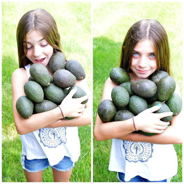 Girl holding a bunch of avocados