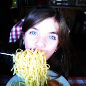 Girl eating pasta and loving it