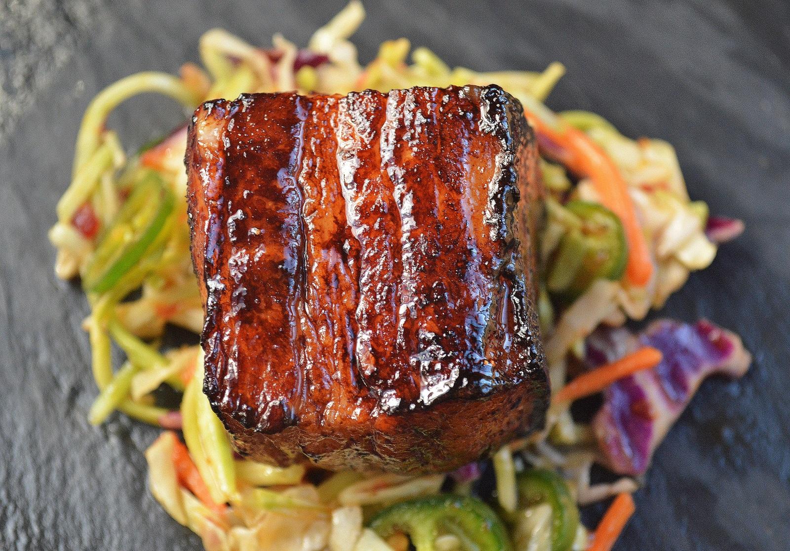 Slow Roasted Pork Belly Bites over Jalapeno Slaw.