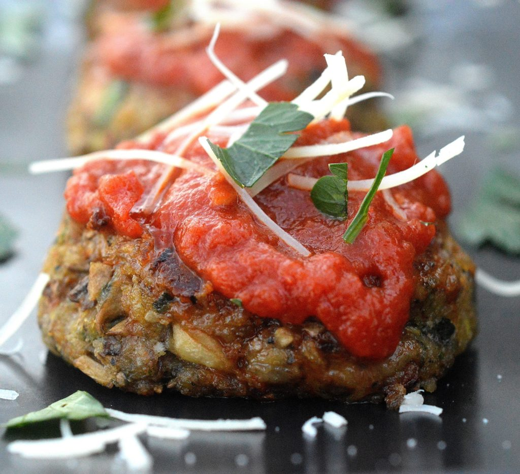 Cheesy Mushroom Meatless Meatballs on a black plate topped with red sauce