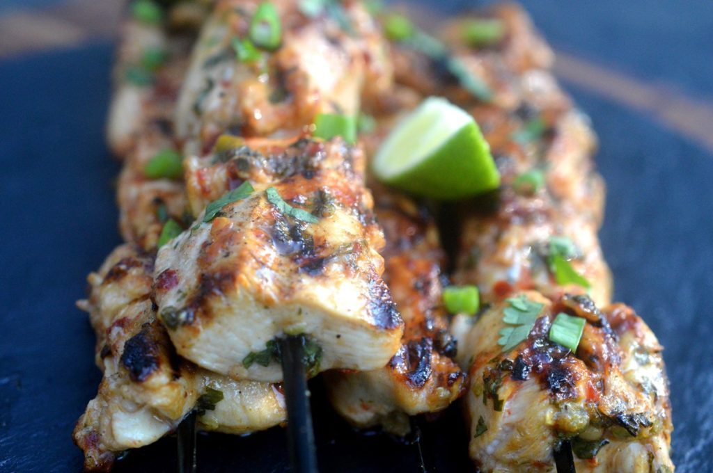 Close up shot of cooked Grilled Chili Lime Chicken Skewers garnished with a lime wedge and fresh cilantro