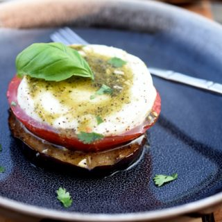 Grilled Eggplant Tomato Mozzarella with pesto in a black bowl topped with basil leaf