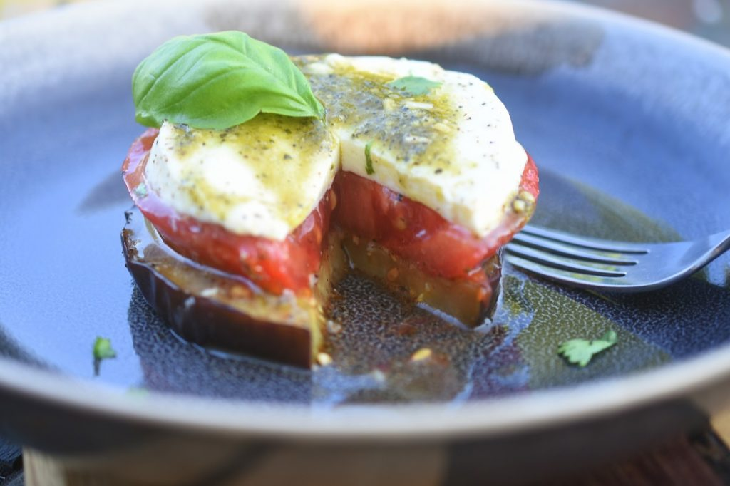 Grilled Eggplant Tomato Mozzarella Stack on black dish sliced open
