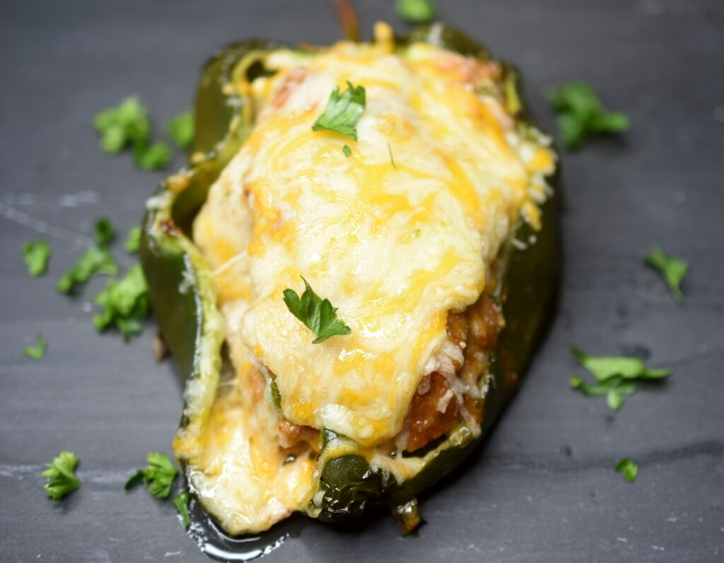 Grilled Meatloaf Stuffed Peppers topped with melted cheese on a stone plate