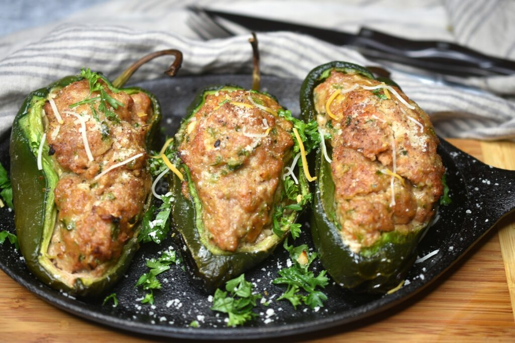 Cooked Grilled Meatloaf Stuffed Peppers on a cast Iron skillet garnished with parsley