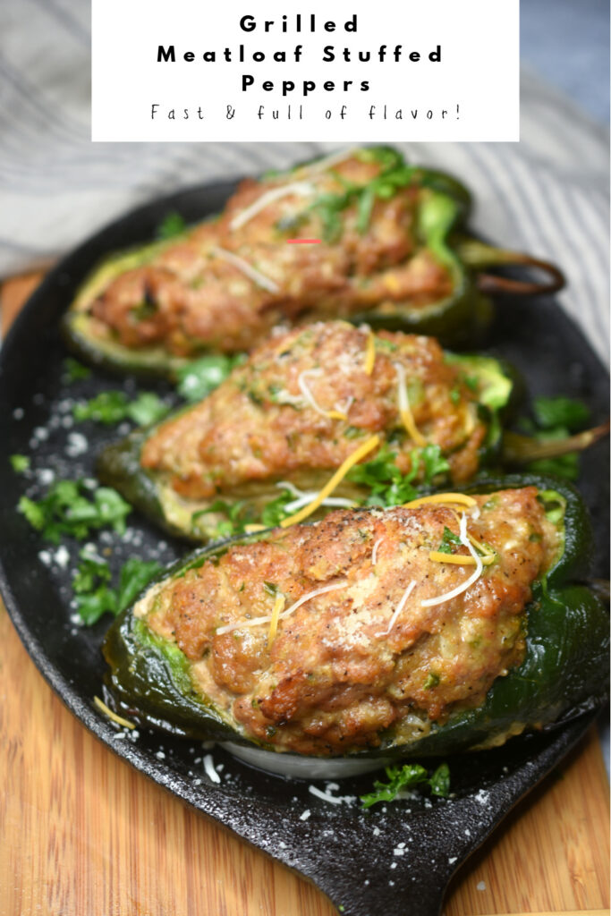 Pinterest image of three cooked Grilled Meatloaf Stuffed Peppers on a cast iron skillet