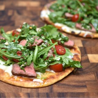 2 Chimichurri Steak Flatbreads on a wooden cutting board