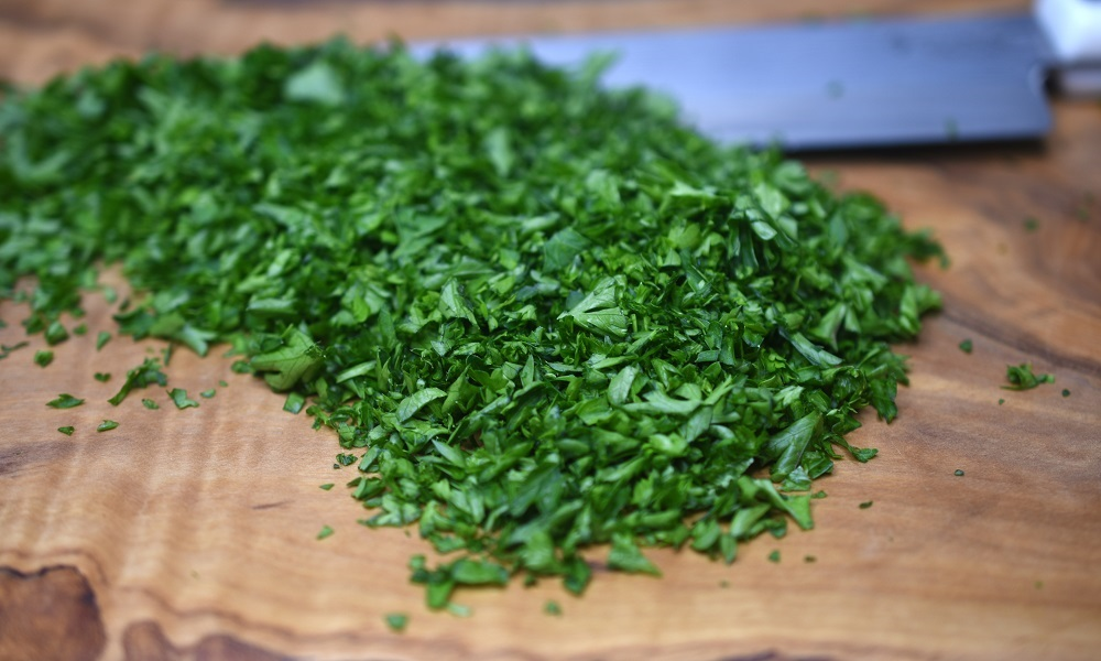 chopped parsley on a cutting board with a knife