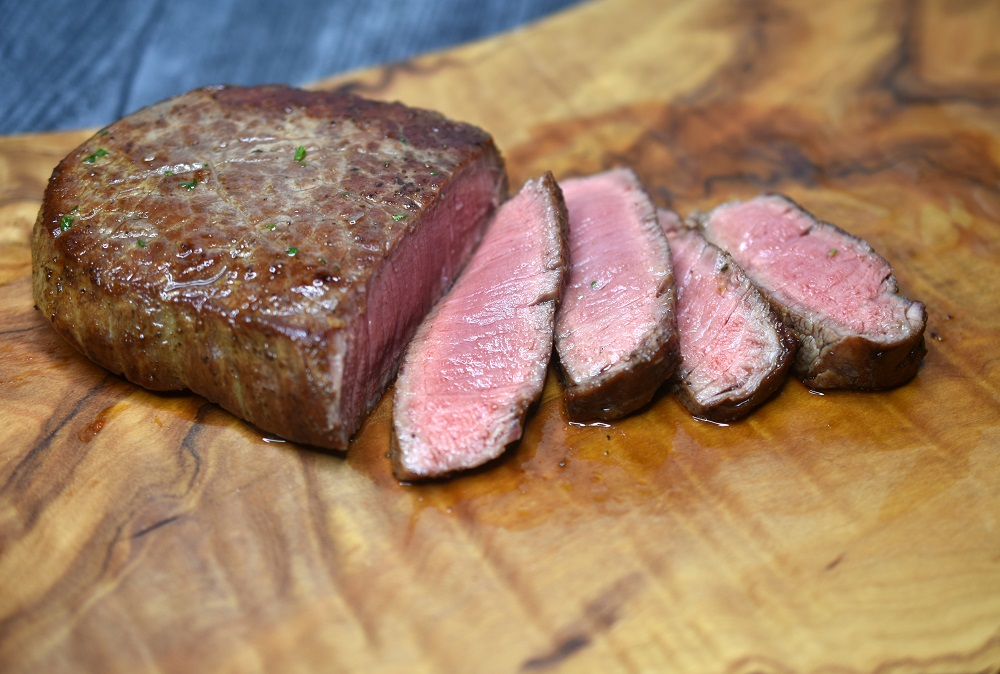 cooked filet mignon steak, sliced on cutting board