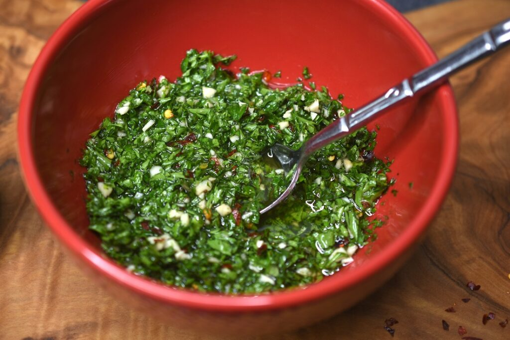 Homemade Chimichurri Sauce in a red bowl with spoon