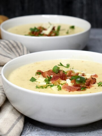 Creamy Potato Soup topped with bacon crumbles in a white bowl